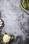 Ackerbohnen, Blumenkohl und Champignons auf grauem Fond