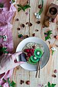 Slices of fresh kiwi and raspberries, chocolate and hazelnuts in bowl of healthy porridge