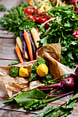 an arrangement of vegetables with beetroot, patty-pan squash, colourful carrots, tomatoes and mizuna