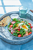 Garden leaves, hot smoked salmon salad with strawberries and poached egg
