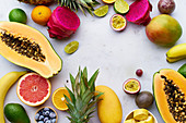 Tropical fruits flat lay with mango, papaya, pitahaya, passion fruit, grapes, limes and pineapples