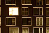 Single lit window in apartment block