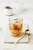 Iced coffee with milk and ice cubes in a glass