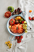 Various colourful tomatoes on a stone surface with an enamel colander and a tea towel