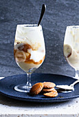 Glasses with banana pudding - sliced bananas, wafer cookies, vanilla pudding, whipped cream and caramel sauce