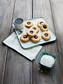 Linzer Plätzchen (nutty shortcrust jam sandwich biscuits with holes on top) with sugar nibs
