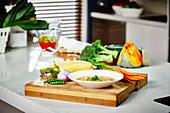 Ein Teller Gemüsesuppe auf Küchentheke umgeben von Zutaten