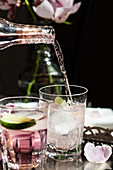 Bottle of pink tonic water (tonic with bitters) being poured into a glass of gin with lime