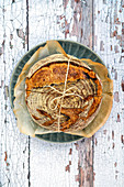 Sourdough loaf tied with twine on a rustic background