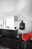 Roter Designerstuhl im Bad in Schwarz und Weiß unter der Schräge