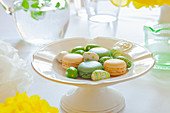 Macaroons and painted mini Easter eggs on a spring-themed Easter table