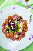 Beef carpaccio with olives, chanterelle mushrooms and parmesan