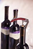 A bottle of red wine being opened with a corkscrew