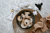 Homemade, gluten-free vanilla biscuits with icing sugar and Froebel stars as Christmas decorations