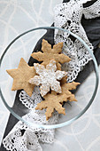 Homemade, gluten-free almond biscuits on a glass plate with a lace doily for Christmas