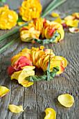 Kränze aus Blütenblättern von Rosen und Chinaschilf
