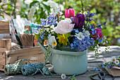 Bunter Frühlingsstrauß im Teekessel: Tulpen, Hyazinthen, Hornveilchen, Traubenkirsche, Vergißmeinnicht, Wolfsmilch und Katzenminze