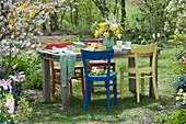 Gedeckter Tisch im Garten mit Strauß aus Narzissen und Blütenzweigen