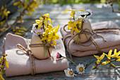 Geschenke zu Ostern : Decken zusammengebunden mit Schnur, Ostereier mit Gänseblümchen und Goldglöckchen als Dekoration