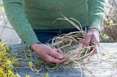 Frau windet Kranz als Osternest aus Gräsern