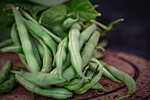 Green runner beans on a wooden plate