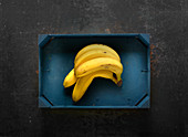 Bananas in a blue wooden crate