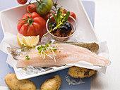 Fresh trout fillets with potatoes, tomatoes and olives