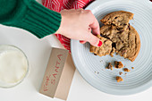 Woman picking up cookie by card for Santa
