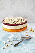 Vegan cake with cashew nut and coconut cream, blackcurrant jelly and popcorn