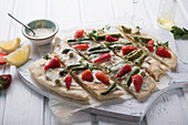 Vegan tarte flambé with cashew nut cream, green asparagus, strawberries and daisies