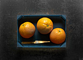 Three oranges in a wooden crate