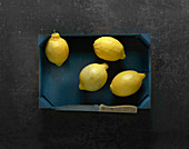 Four lemons in a wooden crate