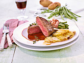 Beef fillet with bacon-wrapped beans and potato gratin