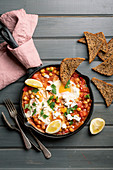 Chickpea shakshouka with feta, parseley, lemon wedges and toasted whole wheat bread