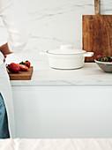 Weißer Kochtopf mit Deckel auf Marmor-Arbeitsplatte