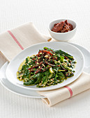 Dandelions with dried tomatoes and pine nuts