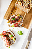 Bread topped with avocado and bacon