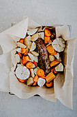 Lamb crown with root vegetables in parchment paper
