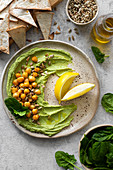 Hummus with spinach, baked chickpeas, sunflower seeds and lemon