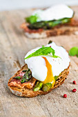 Toasts with green asparagus bacon and poached egg with pouring yolk