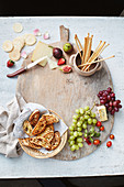 Cheese, toasted bread, breadsticks and fruits on a wooden board
