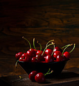 Cherries in a bowl against a dark background