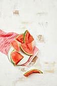 Wassermelonenstücke, eines angebissen