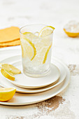 A glass of water with ice cubes and lemon wedges