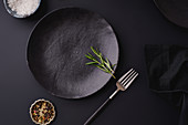 Black dinner setting - empty plates on dark background