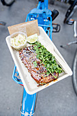 Grilled spare ribs in a cardboard bowl