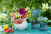 Kleiner Strauß aus Rosen, Hahnenfuß und Goldlack in weißer Kanne, Gläschen mit Gedenkemein und Frauenmantel
