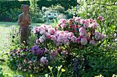 Schattiges Beet mit Rhododendron 'Silberwolke', Funkie, Hornveilchen, Zierlauch 'Ostara' und Akelei, Terracotta-Figur