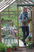Frau bringt Töpfe mit Nelken aus dem Gewächshaus
