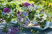 Kleine Sträuße mit Zierlauch 'Ostara', Flieder, Gedenkemein, Waldmeister-Blüten und Weißdorn in Gläsern